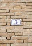 Número tres en una pared de ladrillo Fotografía de archivo