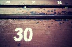 Número trinta pintado em um assento de madeira velho Fotografia de Stock Royalty Free