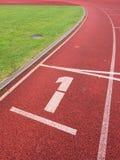 Número um… Número branco da trilha na pista de borracha corrida Fotos de Stock