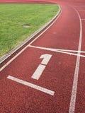 Número um… Número branco da trilha na pista de borracha corrida Fotos de Stock Royalty Free