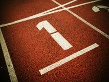 Número um… Número branco da trilha na pista de borracha vermelha Fotografia de Stock