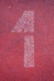Número um na pista de atletismo Número branco da trilha na pista de borracha vermelha Fotos de Stock