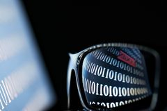 Números binarios que reflejan en las gafas de sol del ordenador portátil imagen de archivo