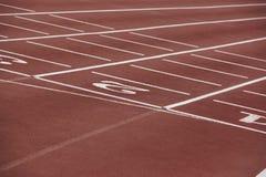 Números blancos en una pista corriente atlética Imagenes de archivo