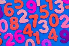 Números coloreados mezclados en un fondo azul Imagen de archivo