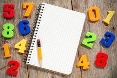 Números coloridos e caderno vazio Fotografia de Stock Royalty Free