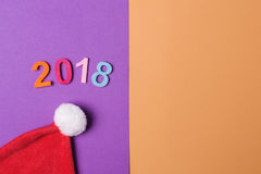 2018 números coloridos e chapéu de Santa no backround de papel, estilo mínimo Foto de Stock Royalty Free