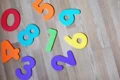 Números coloridos en fondo laminado del piso de la textura de madera marrón clara foto de archivo libre de regalías