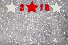 Números de madera que forman el número 2018, por el Año Nuevo y la nieve en un fondo concreto gris Imagen de archivo libre de regalías