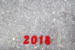 Números de madera que forman el número 2018, por el Año Nuevo y la nieve en un fondo concreto gris Imagen de archivo