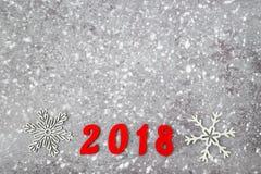 Números de madera que forman el número 2018, por el Año Nuevo y la nieve en un fondo concreto gris Foto de archivo libre de regalías