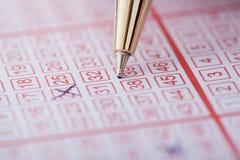 Números de marca de la pluma en boleto de lotería Foto de archivo