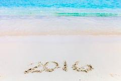 Números del Año Nuevo anotados en la playa Imagen de archivo libre de regalías