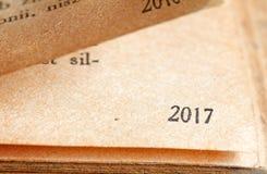 2017 números del Año Nuevo en la página del concepto del fondo del libro Foto de archivo