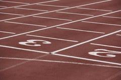 Números dos y poste indicador tres en una pista corriente atlética Imagen de archivo libre de regalías