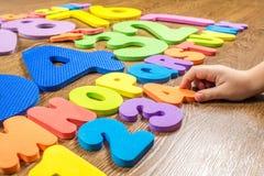 Números e letras plásticos no fundo de madeira Imagens de Stock
