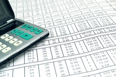 Números en el papel y la calculadora Foto de archivo