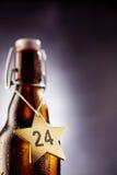 24 números en la estrella marcada con etiqueta de la Nochebuena alrededor de la botella Fotos de archivo libres de regalías