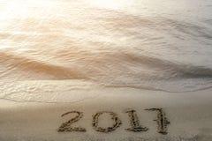 Números 2017 manuscritos en arena de oro en la playa al lado de Foto de archivo