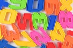 Números plásticos coloridos en blanco Imágenes de archivo libres de regalías