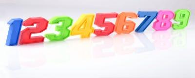 Números plásticos coloridos en un blanco Imagen de archivo libre de regalías