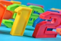 Números plásticos coloridos en un fondo azul Imágenes de archivo libres de regalías