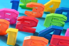 Números plásticos coloridos en un fondo azul Imagen de archivo libre de regalías