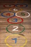 Números redondos do hopscoth no assoalho de madeira fotos de stock royalty free