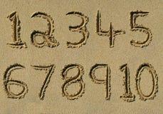 Números uno a diez escritos en una playa arenosa.