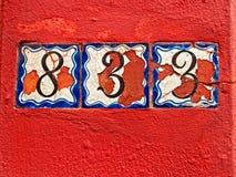 Números velhos em uma parede vermelha Imagem de Stock Royalty Free