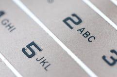 Números y letras en un móvil de oro usado viejo imagen de archivo