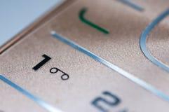 Números y letras en un teléfono móvil de oro usado viejo fotografía de archivo