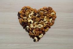 Nüsse auf dem Tisch in einer Herzform Stockfotografie