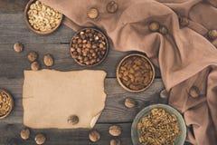 Nüsse in den Schüsseln und im Pergament Lizenzfreie Stockbilder