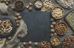 Nüsse in den Schüsseln und im Schieferbrett Lizenzfreies Stockbild