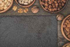 Nüsse in den Schüsseln und im Schieferbrett Stockbild