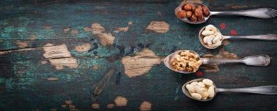 Nüsse in den Weinleselöffeln auf einem Weinlesedunkelheitshintergrund Stockfotos