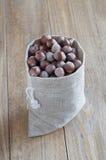 Nüsse in einem alten Schreibtisch des Segeltuchbeutels Lizenzfreie Stockfotografie