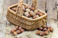 Nüsse in einem Korb auf hölzernem Hintergrund stockbild