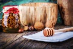 Nüsse im Honig und im Honigschöpflöffel Stockbilder