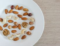 Nüsse, Mandeln, Haselnüsse, Walnüsse, Acajounüsse auf weißer Platte auf einem Holztisch Gesunder organischer Imbiss, Frühstück, N lizenzfreies stockfoto