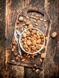 Nüsse mit Nussknacker in einer Schüssel auf dem alten Brett Lizenzfreie Stockfotos