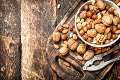 Nüsse mit Nussknacker in einer Schüssel auf dem alten Brett Stockfoto