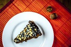 Nüsse mit Stück des Schokoladenkuchens stockfotos