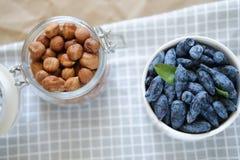 Nüsse und Geißblatt sind auf dem Tisch stockfotografie