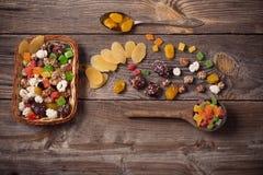 Nüsse und Trockenfrüchte auf hölzernem Hintergrund Stockbild