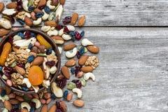 Nüsse und Trockenfrüchte in einer Schüssel über rustikalem Holztisch Lizenzfreie Stockbilder