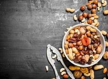 Nüsse und Trockenfrüchte in einer Schüssel mit einem Nussknacker Lizenzfreie Stockbilder