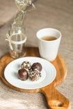 Nützliche Bonbons mit Kokosnuss in der Schokolade und im Tee lizenzfreies stockbild