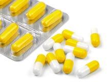 Nützliche gelbe Pillen auf einem weißen Hintergrund Lizenzfreie Stockfotografie